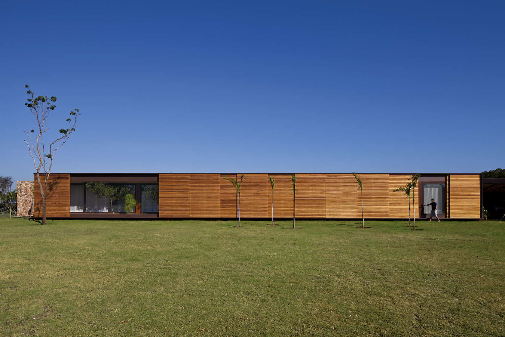 Bedrooms´ volume wooden façade, some blinds opened